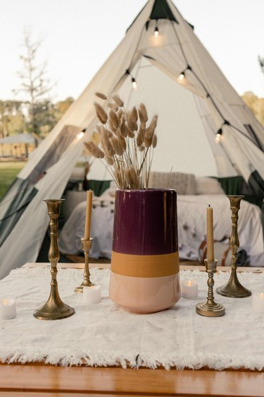 Burgundy, gold and blush striped vase with dried florals and brass candlesticks