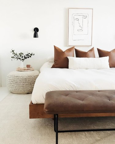 masculine boho bedroom with leather pillows and woven pouf as nightstand