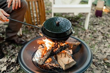 Enamel popcorn popper being held over fire pit flame