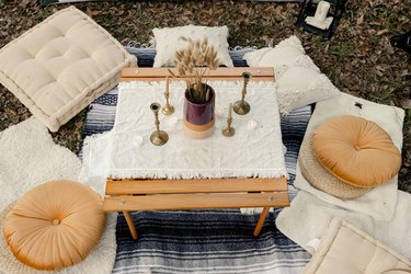 DIY boho glamping loung area with pillows, candles, flowers and poufs