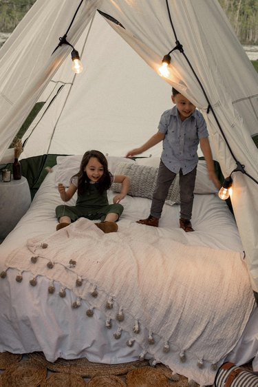 Two kids jumping on bed inside glamping tent