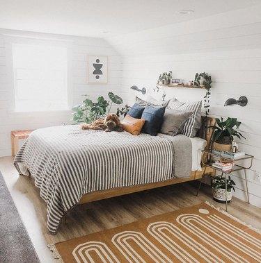 masculine boho bedroom with striped duvet and patterned rug