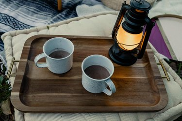 Two enamel camping mugs with hot cocoa on a tray with lantern