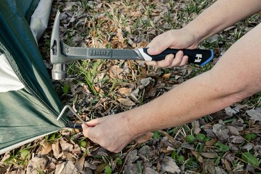 Hammering tent stakes into the ground with HART hammer
