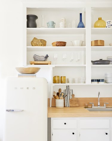 small kitchen storage ideas in all-white space with wood countertops