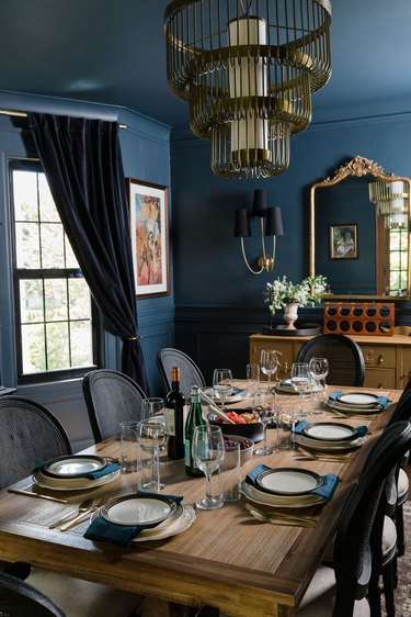Navy blue dining room with brass traditional dining room lighting
