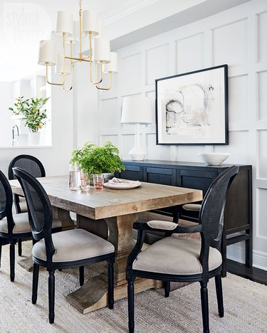 traditional dining room lighting with chandelier above table with black chairs