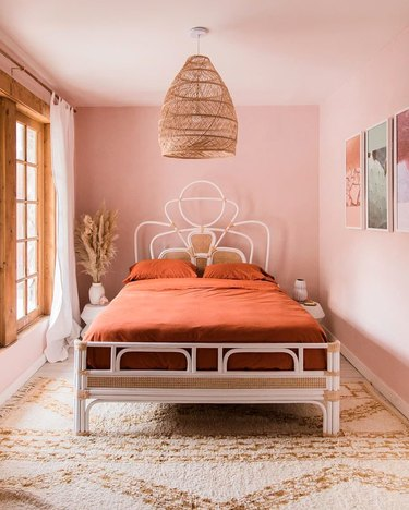 pink and orange desert house color palette in bedroom with rattan pendant