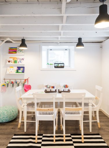 white basement ceiling ideas in kids space with striped rug and white table
