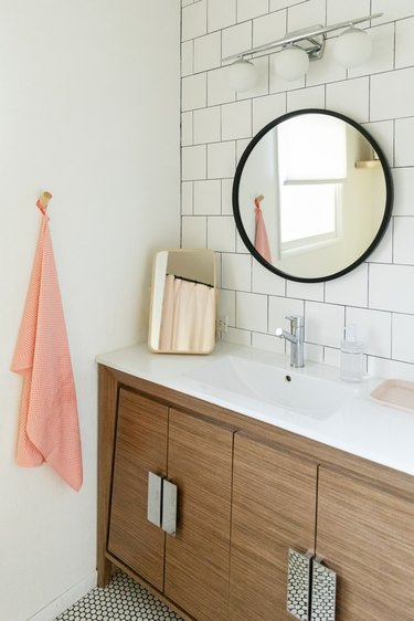bathroom, white subway tile wall, wood vanity with white ceramic vanity top, silver faucet, round mirror with black trim, pink hanging towel