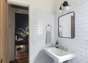 bathroom with white subway tile wall, black square mirror, black light fixture, pedestal sink, black and white striped hand towel