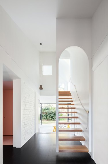 white entry with floating stairs and windows at the end of the hall