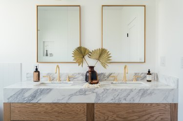 wood bathroom vanity with marble counters, double sinks with gold fixtures, two rectangular mirrors with gold trim