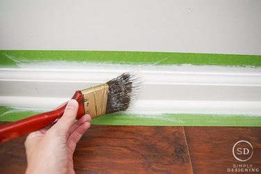 Baseboards being painted.