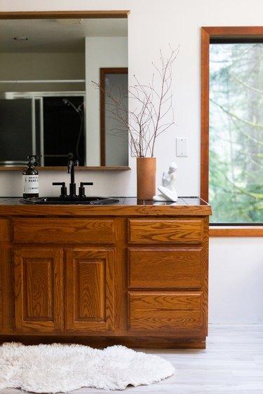 wood vanity, rectangular mirror with wood trim, small fur rug, light hardwood vinyl flooring
