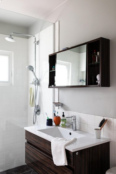 glass shower with white square tile, small wood vanity with white ceramic top, built-in medicine cabinet with mirror and wood shelves