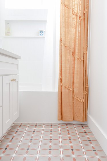 small bathroom with vinyl floor with orange, black and white pattern, white vanity, white bathtub, orange shower curtain