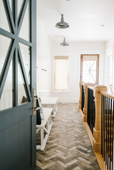 Warm wood and black wrought iron farmhouse stair railing in breezeway