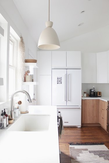 Modern kitchen lighting idea with pendant light over sink and two tone cabinets