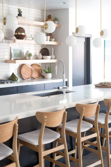 modern kitchen lighting idea paired with blue cabinets and open shelving