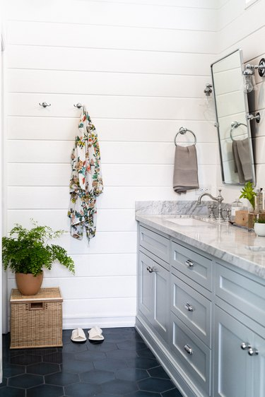 light blue painted bathroom cabinets, marble countertop, silver rectangular mirror, blue hexagon tile floor, rattan box, green plant, floral towel hung up