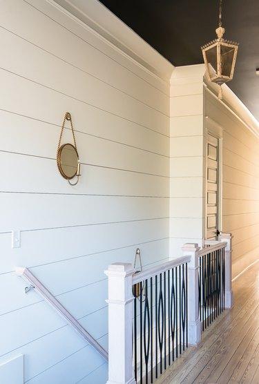 Black wrought iron farmhouse stair railing with white shiplap wall