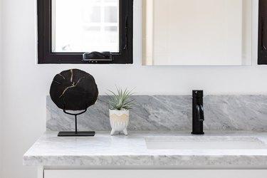 quartz bathroom countertop, black faucet, white vase with green plant, black decorative stand