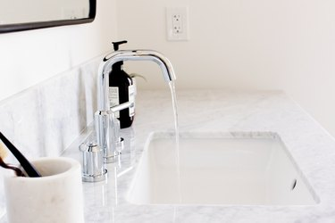 undermount sink with silver faucet, quartz countertop, white toothbrush holder