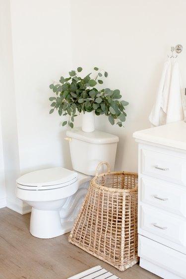 white toilet, rattan basket, white vanity with silver drawer pulls, white towel, white vase with eucalyptus leaves, light wood vinyl flooring
