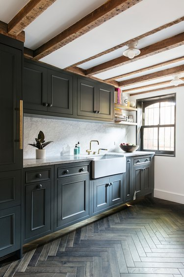 basement kitchen with exposed beams and dark cabinets