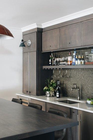 basement kitchen with gray penny tile backsplash and liquor shelf