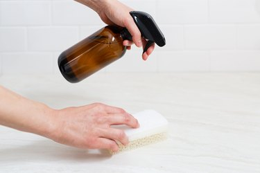 Hands holding brown spray bottle and sponge