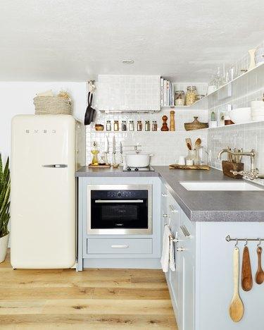 basement kitchen with blue cabinets and cream Smeg fridge