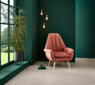 room with deep green walls and pink chair