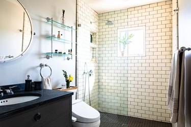 vanity with undermount sink and black vanity top, round mirror, glass shelves, white toilet, walk-in shower with glass door, subway tile wall, black hexagon shower tile floor
