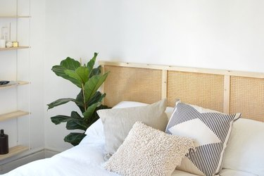 Headboard for boho bed using IKEA Ivar panel and cane webbing.