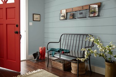 entryway with red door and eggshell blue wall and black bench