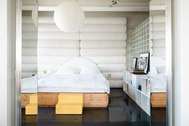 bedroom with glossy black concrete floors, large pendant light, oversized headboard