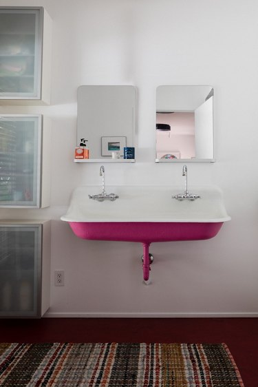 pink cast-iron wall-mounted sink with white interior,