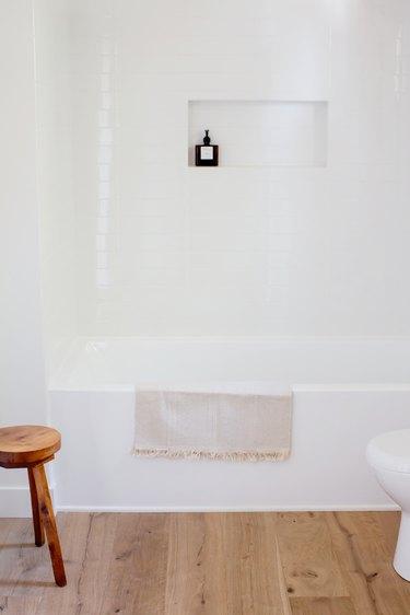 white vinyl bathtub and shower installation, wood vinyl planks, wood stool
