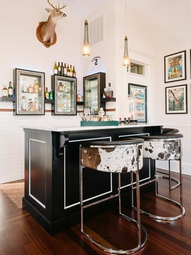 black basement bar with class wall cabinets and wall art