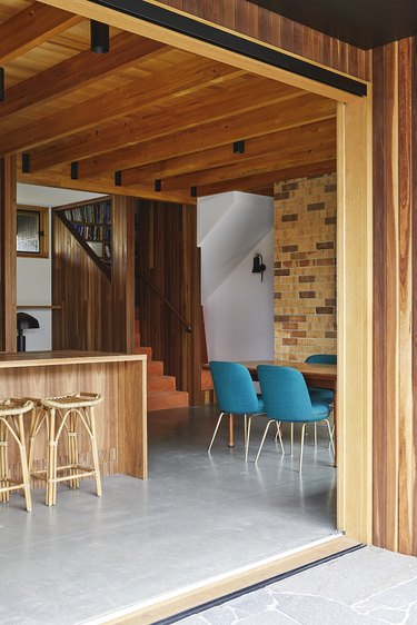 wood basement furniture with bar, rattan bar stools, and blue dining chairs