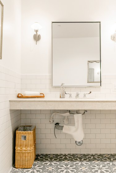 white bathroom with wall-hung sink, rectangular mirror,  subway tile wall, vinyl flooring with a floral pattern, rattan basket, light sconces