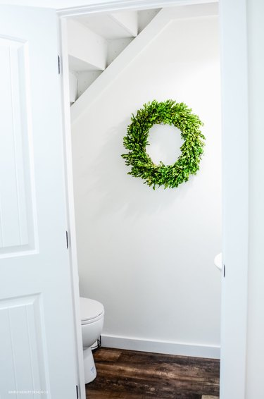 Bathroom under stairs with white walls and green boxwood wreath