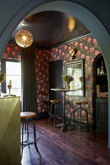 black basement bar with floral wallpaper and bistro table set