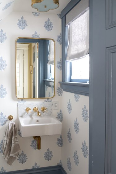 blue and white bathroom under stairs with wall-mounted sink and brass fixtures