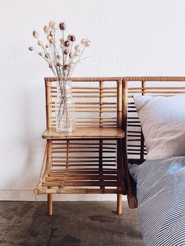 vintage bamboo daybed with striped duvet and vase of flowers