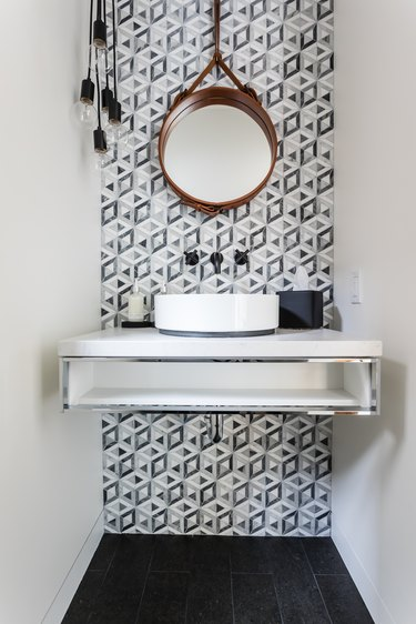 Bathroom under stairs with gray and white modern backsplash and round mirror