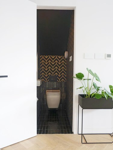 Bathroom under stairs with black tile and a gold chevron wall