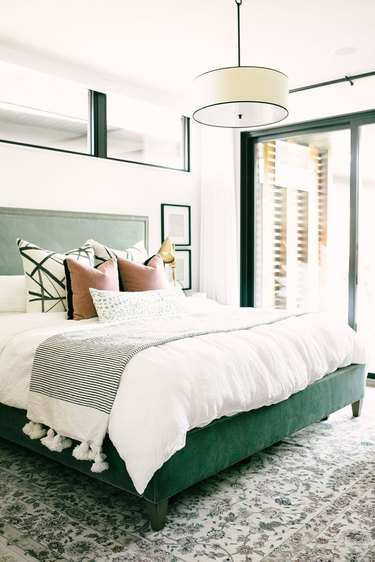 neutral bedroom idea with hanging pendant light and green upholstery